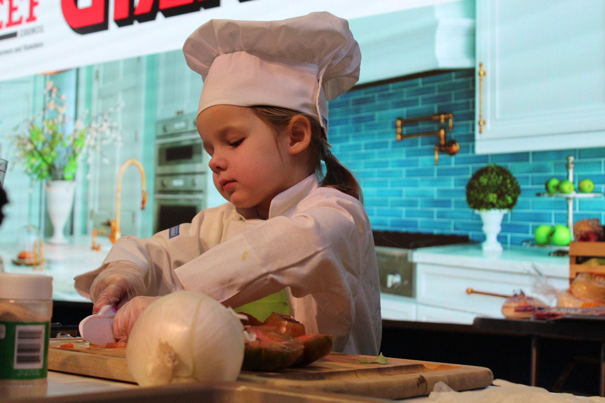 A young girl dressed as a chef and cooking at the 2020 Pennsylvania Farm Show.